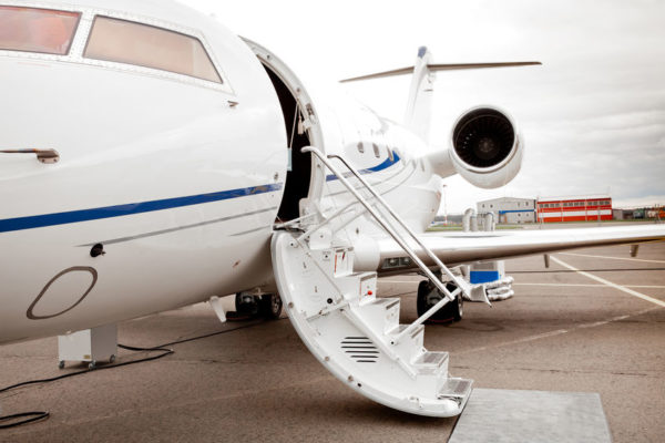 White private business jet and open ladder at the airport